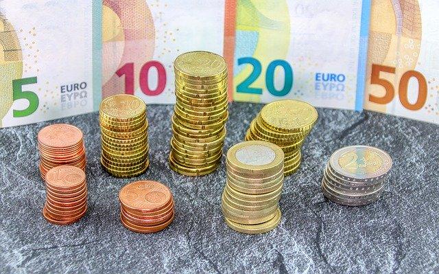 sloupečky mincí, v pozadí stojí bankovky