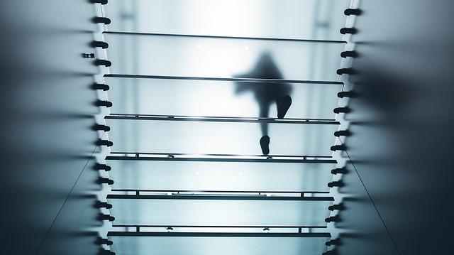 skleněné schodiště v bytě s člověkem kráčejícím nahoru.jpg