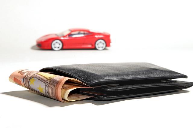 peněženka s penězi, červené auto v pozadí